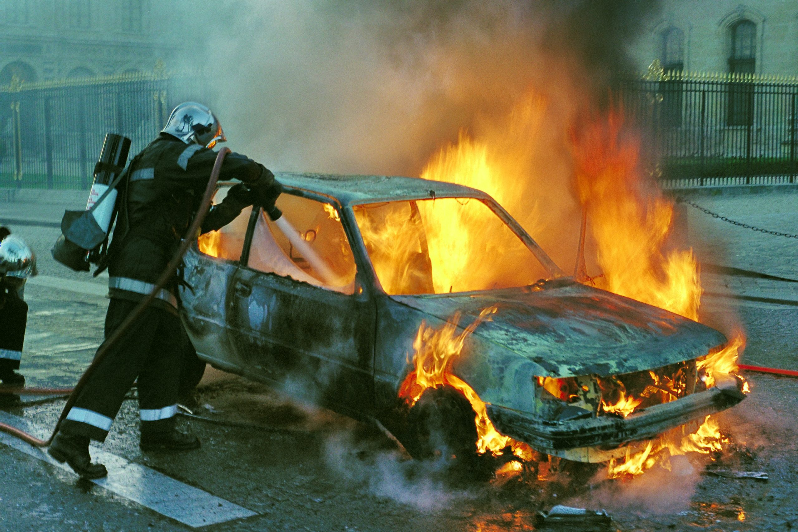 Firefighter putting out a burning car